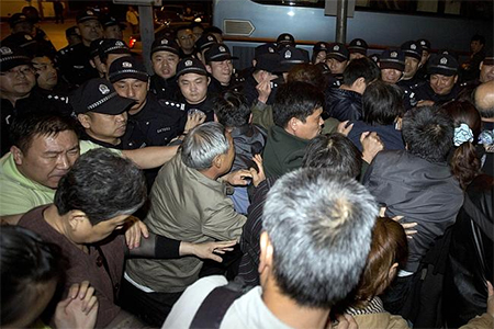 Fury ... Relatives of Chinese passengers on-board the Malaysia Airlines MH370 push through a police line to march to the Malaysian embassy from a hotel in Beijing