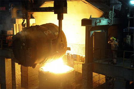 Workers look at a ladle pouring molten iron into a container at a steel plant in Hangzhou, Zhejiang province