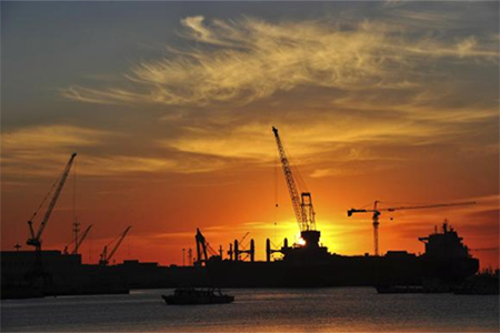 A shipyard is silhouetted against the rising sun in Dalian, Liaoning province
