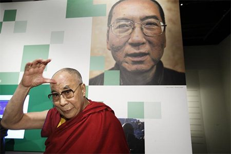 The Dalai Lama is seen during a visit to the Nobel Peace Center in Oslo May 9, 2014. On the wall is a portrait of 2010 Nobel Peace Prize winner Liu Xiaobo from China, which is part of an exhibition at the Nobel Peace Centre