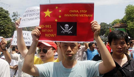 Protesters hold anti-China placards while marching in an anti-China protest on a street in Hanoi May 11, 2014