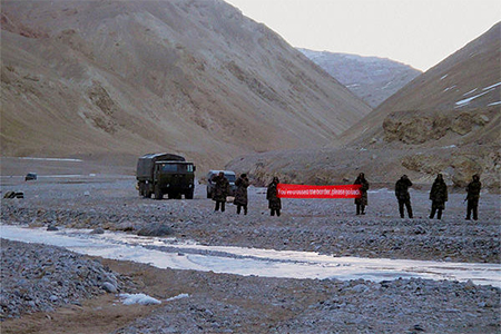"Chinese troops hold a banner which reads: ""You've crossed the border, please go back"" in Ladakh, India. India is raising a new mountain strike corps consisting of some 90,000 soldiers to strengthen its defence along its disputed but largely uninhabited border with China in the high reaches of the Himalayas. Photo taken Sunday, May 5, 2013."