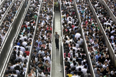 Passengers line up and wait for a security check during morning rush hour at Tiantongyuan North Station in Beijing. Photos: Reuters
