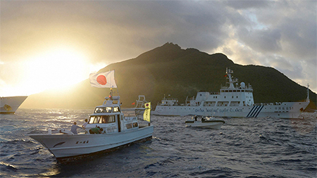 Chinese marine surveillance ship Haijian No. 51 (C) sails near Japan Coast Guard vessels (R and L) and a Japanese fishing boat (front 2nd L) as Uotsuri island, one of the disputed islands, called Senkaku in Japan and Diaoyu in China