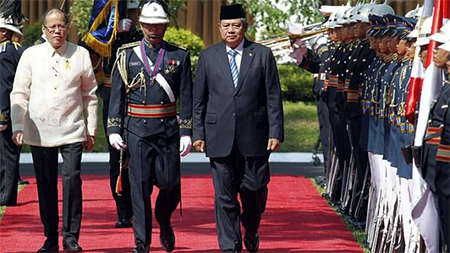 Philippine President Benigno Aquino (left) and visiting Indonesia President Susilo Bambang Yudhoyono (right) reviewing honour guards at the presidential palace in Manila on May 23, 2014