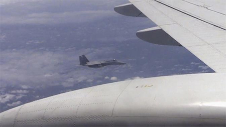 A Japanese F-15 jet (background) and a Chinese Tu-154 jet (foreground) fly over the East China Sea, in this still image from video footage released by China's Ministry of Defence on June 12, 2014