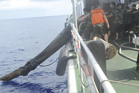 Chinese maritime policemen on Chinese Coast Guard ship 44101 pull a wooden log, which according to Chinese authorities was placed in the waters by Vietnam on purpose as obstacles, in South China Sea, in this handout dated May 5, 2014 provided by Chinese Ministry of Foreign Affairs June 13, 2014
