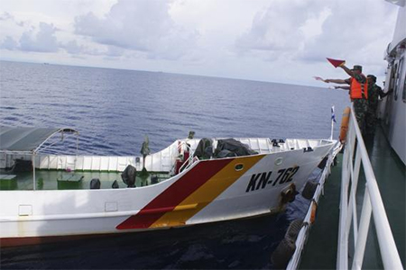 A Chinese maritime policeman (R) uses flags to signal to Vietnamese ship KN-762 (L), which according to Chinese authorities collided with Chinese coast guard ship 46001 in South China Sea, in this handout dated May 2, 2014 provided by Chinese Ministry of Foreign Affairs on June 13, 2014