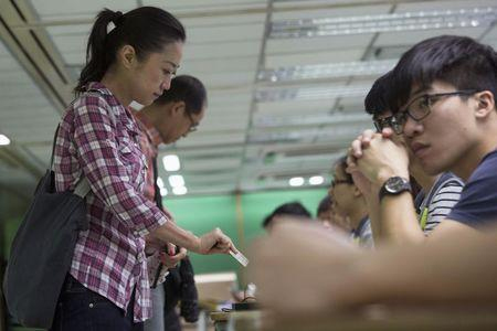 A woman presents her ID card to a poll assistant during a civil referendum held by the Occupy Central organisers at polling station in Hong Kong June 22, 2014