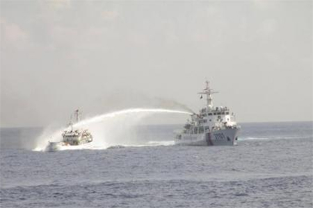 A Chinese ship (R) uses water cannon on a Vietnamese Sea Guard ship on the South China Sea near the Paracels islands, in this handout photo taken on May 5, 2014 and released by the Vietnamese Marine