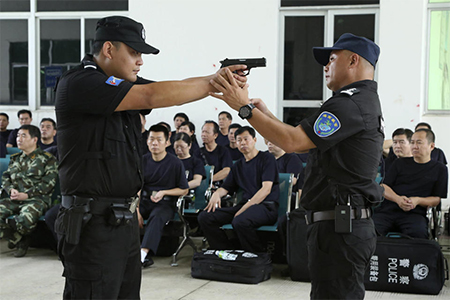 A police training officer, right, guides a trainee during a weapons training session for police officers in Haikou, in southern China's Hainan province
