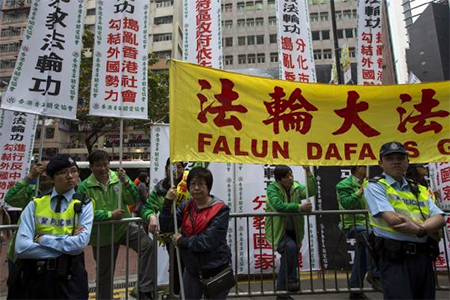 Policemen look on as supporters of 'Care for the Youth Group Association Hong Kong' (CYGAHK) carrying white banners protest against supporters of Fa Lun Gong holding a yellow banner at a shopping district in Hong Kong March 16, 2014