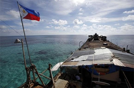 A Philippine national flag flutters in the wind aboard the BRP Sierra Madre, run aground on the disputed Second Thomas Shoal, part of the Spratly Islands, in the South China Sea