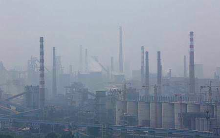 A steel factory is seen in smog during a hazy day in Anshan, Liaoning province, June 29, 2014