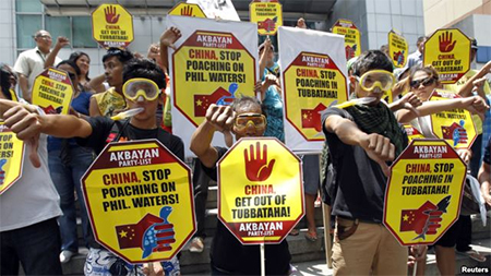 Protesters wearing snorkels and masks show the thumbs-down sign during a protest rally in front of the Chinese Consular office at the financial district of Makati city, metro Manila, April 10, 2013