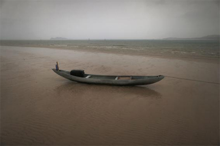 A fishing boat sits on a beach during a rain storm on the east coast of Natuna Besar July 7, 2014