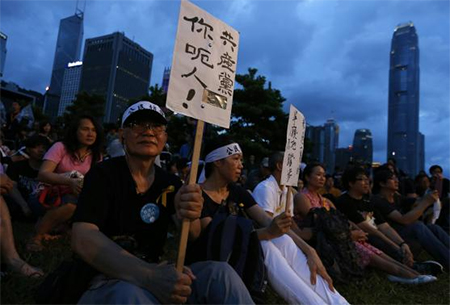 A pro-democracy protester carries a placard which reads 'Communist Party, you lie!' as he sits with other protesters during a campaign to kick off the Occupy Central civil disobedience event in front of the financial Central district in Hong Kong August 31, 2014.