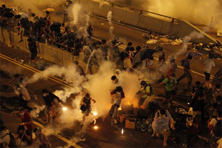 Riot police fire teargas to disperse protesters after thousands of demonstrators blocked the main street to the financial Central district outside the government headquarters in Hong Kong September 29, 2014.