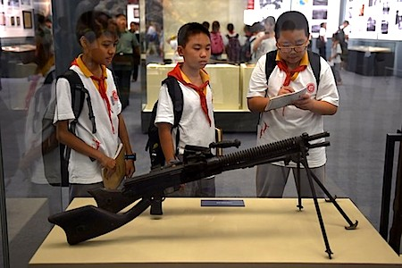 Chinese children look at weapons used by the Japanese military in World War II at an exhibition about the war, in Beijing on Sept. 3.