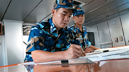 Vietnamese coast-guard crewmen plot coordinates.
