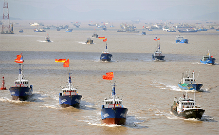 Fishing boats are seen departing from Shenjiawan port in Zhoushan, Zhejiang province towards the East China Sea fishing grounds
