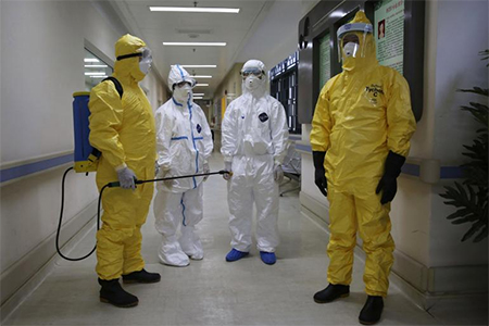 Health workers in protection suits wait in the corridor near a quarantine ward during a drill to demonstrate the procedures of handling Ebola victims at a hospital in Guangzhou, China, Oct. 16, 2014.