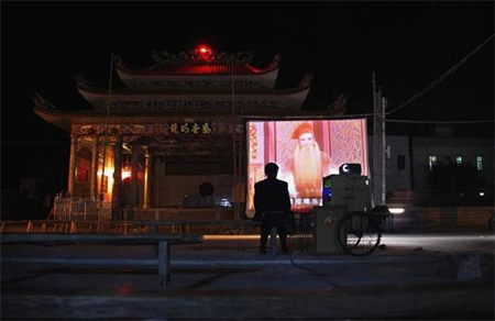 A man sits next to a mobile projector showing a Chinese opera film in front of the local theatre building in the village of Wukan in Lufeng county, Guangdong province