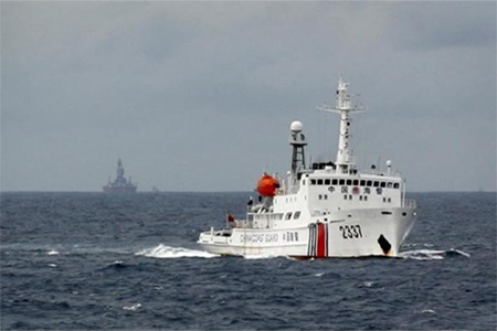 A Chinese Coast Guard vessel (R) passes near the Chinese oil rig, Haiyang Shi You 981 (L) in the South China Sea, about 210 km (130 miles) from the coast of Vietnam June 13, 2014.