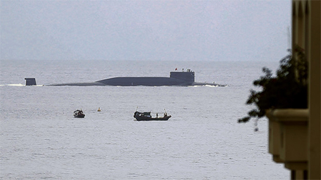 Fishermen look at a Chinese nuclear submarine sails past Yalong Bay in Sanya, south China's Hainan Province.