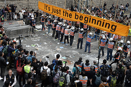 December 11, 2014: Onlookers watch as workers dismantle barricades built by pro-democracy demonstrators at the main protest site in the Admiralty district in Hong Kong.