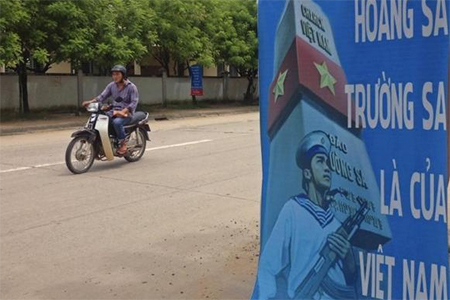A man rides a motorcycle past a poster promoting Vietnam' sovereignty in the East Sea (South China Sea) on Phu Quoc island