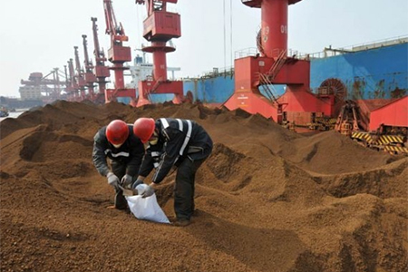 Employees from the local Entry-Exit Inspection and Quarantine Bureau collect samples at an iron ore dump site of Rizhao Port in Rizhao, Shandong province.