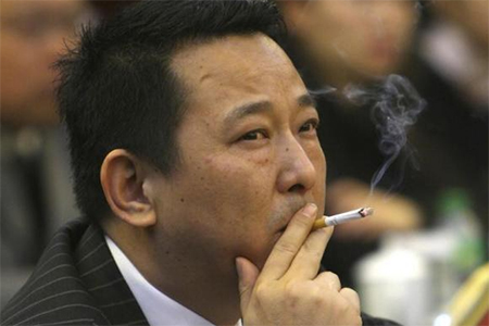 Liu Han, former chairman of Hanlong Mining, smokes a cigarette during a conference in Mianyang, Sichuan province, in this picture taken March 21, 2008.