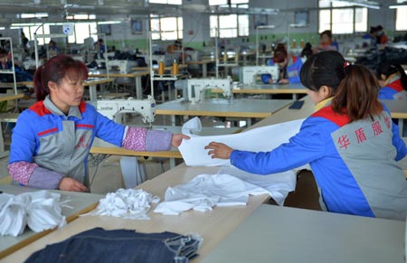 Workers at a clothing processed production line at a factory in Gansu province