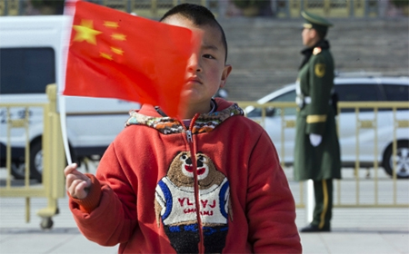 A child poses for photos with a Chinese national flag near the Great Hall of the People in Beijing. Goldman partner Roy Smith sees problems for China such as the burden of an ageing population, with mounting pension and health-care costs. Photo: AP