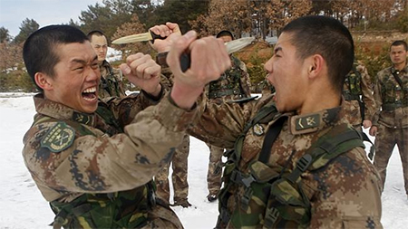 Soldiers from China's People's Liberation Army thrust daggers at each other during a training session.