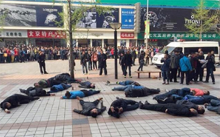 The taxi drivers lie unconscious outside the shopping mall in Wangfujing. Police said they were out of danger.