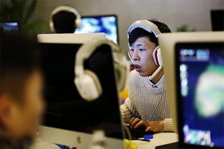 People use computers in an internet cafe in Beijing