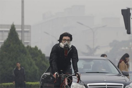 A man wearing a respiratory protection mask cycles along a road amid the heavy haze in Beijing
