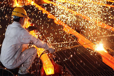 A worker cuts steel billets at an iron and steel enterprise on June 9, 2014 in Ganyu County, China.