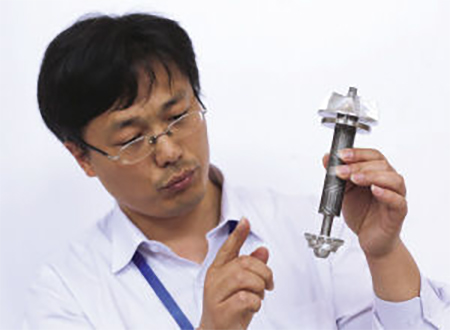 A research worker holding a 10kW/20K helium turbine rotor, a key part of the liquid hydrogen refrigeration device