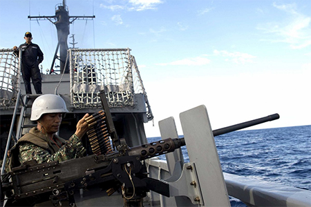 A Philippine Navy personnel loads bullets for a .50 calibre machine gun during the bilateral maritime exercise between the Philippine Navy and U.S. Navy dubbed as Cooperation Afloat Readiness and Training (CARAT) in the South China Sea near waters claimed by Beijing June 29, 2014.