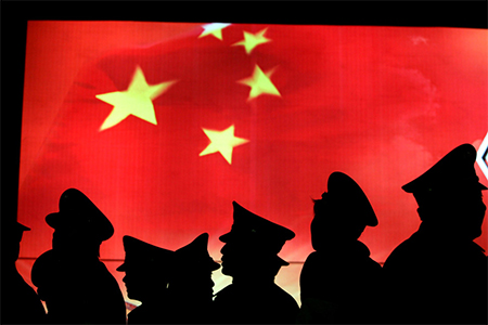 Security guards walk past the Chinese national flag at the Military Museum of Chinese People's Revolution on March 1, 2008 in Beijing, China.