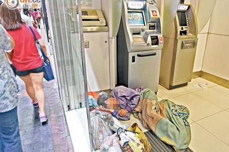 An elderly homeless person sleeping in an ATM centre