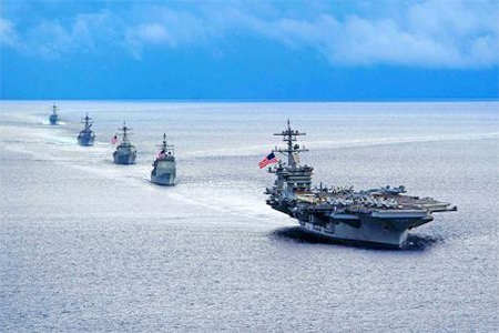 The aircraft carrier USS Theodore Roosevelt leads a formation of ships during a manoeuvring exercise in the Atlantic Ocean.