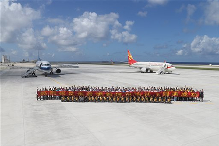 In this Wednesday, Jan. 6, 2016 photo released by China's Xinhua News Agency, people pose for a group photo together after landing at the airfield on the Spratly Islands, also known as Nansha Islands in Chinese, of the South China Sea. A pair of Chinese civilian jet airliners landed at the newly created island in a disputed section of the South China Sea in a test to see whether its airstrip was up to standard, state media reported Thursday, Jan. 7. The China Daily newspaper said the two planes on Wednesday made the two-hour flight to Fiery Cross Reef from Haikou on the southern island province of Hainan.