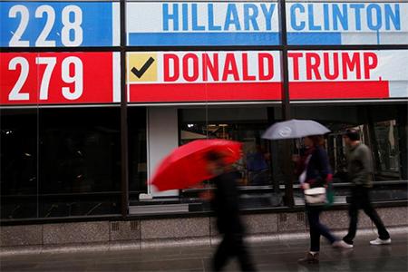 People walk by an electronic billboard in New York U.S., November 9, 2016. REUTERS/Shannon Stapleton