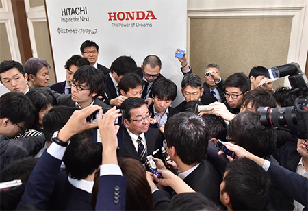 Honda Motor President, CEO and representative director Takahiro Hachigo (C) answers questions following a press conference in Tokyo.
