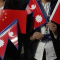 Government officers hold Chinese and Nepalese flags