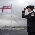 A British naval officer looks up at the fluttering White ensign flag